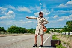 Schönes junges Mädchen oder Frau in Mini mit Koffer per Anhalter fahrend entlang einer Straße - Retrostil Stockfotografie