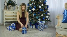 Schönes junges Mädchen setzt Geschenke unter einen Weihnachtsbaum stock footage