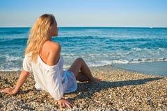 Schönes junges Mädchen sitzen und schauen zum Meer Stockfotos