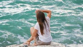 Schönes junges Mädchen sitzt auf den Felsen, richtet ihr Haar gerade und genießt eine Auffrischungsbrise und eine schöne Ansicht  stock footage