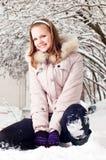 Schönes junges Mädchen sitzt ein, um zu schneien Stockfotos