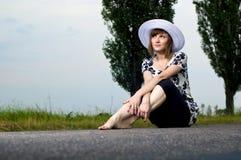 Schönes junges Mädchen sitzt in einem Hut Stockfoto