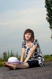 Schönes junges Mädchen sitzt in einem Hut Stockbild