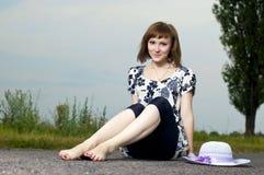 Schönes junges Mädchen sitzt in einem Hut Lizenzfreie Stockbilder