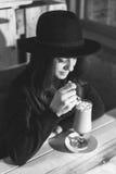 Schönes junges Mädchen in trinkendem Kaffee des Hutes im Café Stockfoto