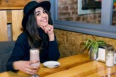 Schönes junges Mädchen in trinkendem Kaffee des Hutes im Café Stockbild