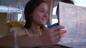 Schönes junges Mädchen wählt Lebensmittel auf der Speisekarte aus und sitzt in einem Café mit einem Glas Wein HD, 1920x1080, Zeit stock video footage