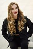 Schönes junges Mädchen, welches die schwarze Jacke sitzt in der Straße trägt Stockfotografie