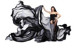 Schönes junges Mädchen, wenn schwarzes Kleid geflogen wird Flüssiges Gewebe Stockbild