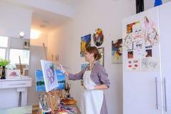 Schönes junges Malerfarbenbild benutzt Bürsten und Öl und Lizenzfreie Stockfotografie
