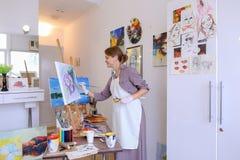 Schönes junges Malerfarbenbild benutzt Bürsten und Öl und Stockfotografie