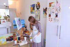 Schönes junges Malerfarbenbild benutzt Bürsten und Öl und Lizenzfreies Stockbild