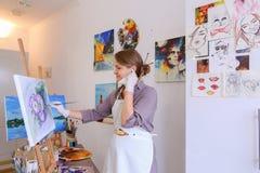 Schönes junges Malerfarbenbild benutzt Bürsten und Öl und Stockfoto