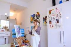 Schönes junges Malerfarbenbild benutzt Bürsten und Öl und Stockfotos