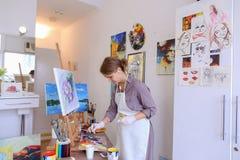 Schönes junges Malerfarbenbild benutzt Bürsten und Öl und Stockbilder