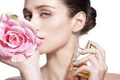 Schönes junges Modell, das einen Blumenduft auf ihrem Körper sprüht stockfoto