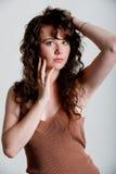 Schönes junges Modell mit dem langen gelockten Haar, das in einem Studio aufwirft Stockfotografie