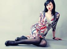 Schönes junges Modell mit dem langen schwarzen Haar, das auf Boden sitzt Stockfoto