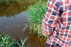 Schönes junges Paar fischt im Fluss an einem Sommertag stockfotografie