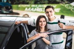 Schönes junges Paar ist, betrachtend lächelnd und Kamera beim Lehnen auf ihrem Neuwagen in einer Autoausstellung Mann hält Autosc lizenzfreie stockbilder
