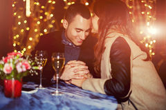 Schönes junges Paarhändchenhalten auf einem romantischen Abendessen in einem Restaurant Stockbild
