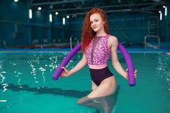 Schönes junges rothaariges Mädchen in einem modernen Badeanzug im Stil der achtziger Jahre Stände mit den Nudeln in ihren Händen  stockbild