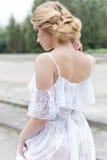Schönes junges süßes blondes Mädchen mit Hochzeitsblumenstrauß in den Händen des Boudoirs in einem weißen Kleid mit Abendfrisur g Lizenzfreies Stockfoto