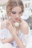 Schönes junges süßes blondes Mädchen mit Hochzeitsblumenstrauß in den Händen des Boudoirs in einem weißen Kleid mit Abendfrisur g Stockbild