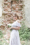 Schönes junges süßes blondes Mädchen mit Hochzeitsblumenstrauß in den Händen des Boudoirs in einem weißen Kleid mit Abendfrisur g Stockfotografie