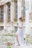 Schönes junges süßes blondes Mädchen mit Hochzeitsblumenstrauß in den Händen des Boudoirs in einem weißen Kleid mit Abendfrisur g Lizenzfreie Stockfotos