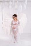 Schönes junges schwangeres Mädchen mit großem Engel beflügelt stockfoto