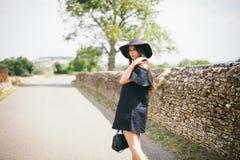Schönes junges sexy Frauenmodell von Brunette mit dunkler Haut im schwarzen Kleid und im Hut mit Feldern, modern gekleidete Stell Stockfoto
