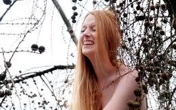 Schönes junges sexy Mädchen mit dem schönen herrlichen roten Haar laut lachend in einem Baum w lizenzfreies stockfoto