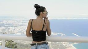 Schönes junges touristisches Mädchen mit Rucksack nahe Meer
