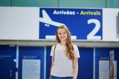 Schönes junges touristisches Mädchen mit Rucksack und machen Gepäck im internationalen Flughafen weiter Lizenzfreies Stockbild