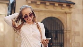 Schönes junges tragendes weißes Hemd der Geschäftsfrau und mit Smartphone beim Gehen in das Internet des Stadtzentrum-Sommers stock video footage