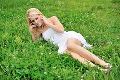 Schönes junges weibliches blondes Modell, das auf dem Gebiet des Klees legt Stockfotos