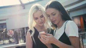 Schönes junges weibliches shopaholics zwei, welches das Internet auf der Suche nach Rabatten im Einkaufszentrum, junge Studentenm stockbilder
