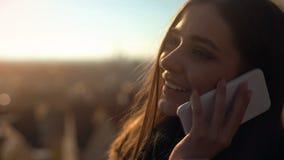 Schönes junges weibliches Unterhaltungstelefon auf dem skydeck, das die Eindrücke, durchstreifend teilt stockbild