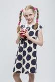 Schönes kaukasisches blondes Mädchen mit den Zöpfen, die in der Polka Dot Dress Against White aufwerfen Stockfoto