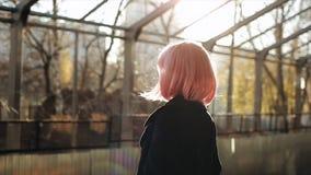 Schönes kaukasisches junges Mädchen mit dem rosa Haar und schwarze Mantelstellung am Bahnhof Attraktive Frauen-Stellung stock footage