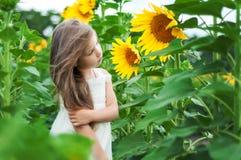Schönes kaukasisches kleines Mädchen auf einem Gebiet mit Sonnenblumen Lizenzfreie Stockbilder