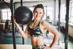 Schönes kaukasisches Mädchen, das einen Ball in der Turnhalle hält Angekleidet in der Spitze und in den kurzen Hosen lizenzfreie stockbilder