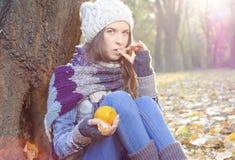 Schönes kaukasisches Mädchen, das Tangerine im Park isst stockfotos