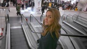 Sch?nes kaukasisches M?dchenl?cheln, gehend die Rolltreppe im Mall hinunter Vor dem hintergrund der unerkannten K?ufer stock video