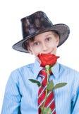 Schönes Kind, das einen Hut und eine Bindung halten ein rotes Rosenlächeln trägt Lizenzfreies Stockbild