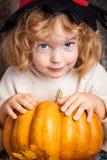 Schönes Kind, das einen Kürbis anhält stockfotografie