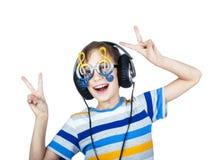 Schönes Kind, das große Berufskopfhörer und lustige Gläser trägt Stockbilder