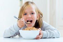 Schönes Kind, das zu Hause frühstückt Stockbilder