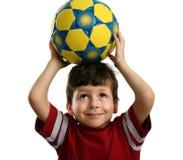 Schönes Kind hält eine Fußballkugel über seinem Kopf an Lizenzfreies Stockfoto